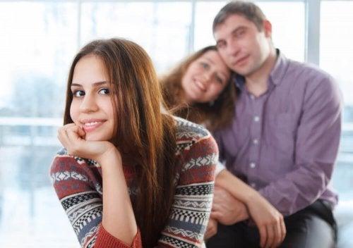 Filha adolescente feliz, com os pais ao fundo