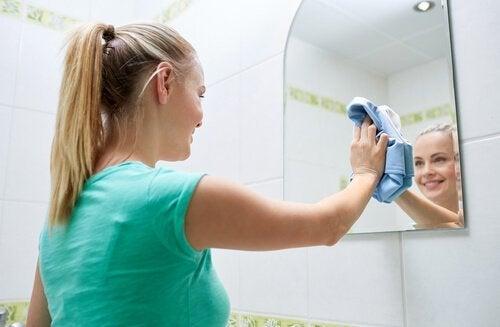 Moça fazendo limpeza do banheiro