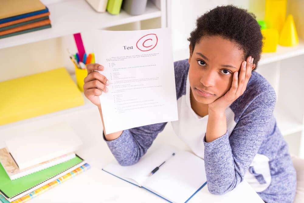 Menina mostrando prova com nota baixa