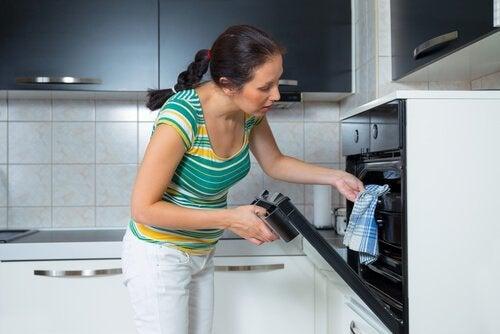 Mulher tirando o suflê de presunto e queijo do forno