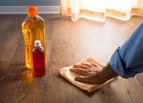 Pessoa limpando marcas de copos na madeira