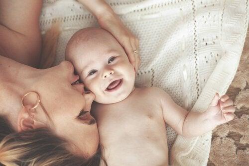 Mãe dando massagens para bebês e carinho ao filho
