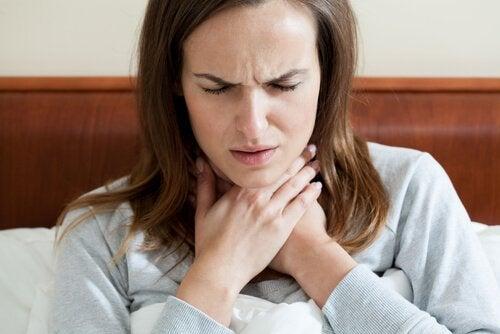 Mulher com dor de garganta precisa de remédio com água morna e mel