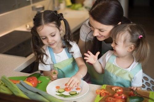 Meninas preparando pratos adequados para o desenvolvimento ósseo de crianças