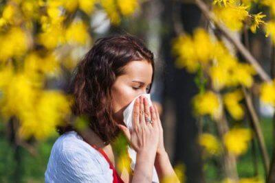 Moça espirrando pela alergia ao pólen