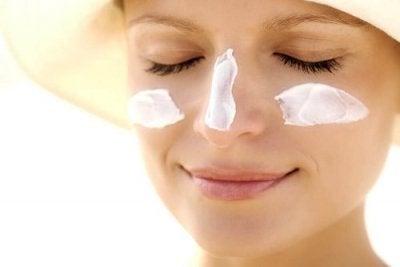 Mulher usando protetor solar contra o melasma