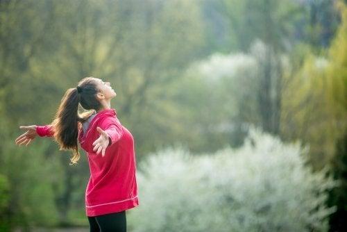 Mulher fazendo exercícios de respiração com braços abertos