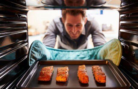 Homem tirando salmão do forno