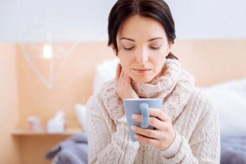 Mulher tomando chá para aliviar a infecção na garganta