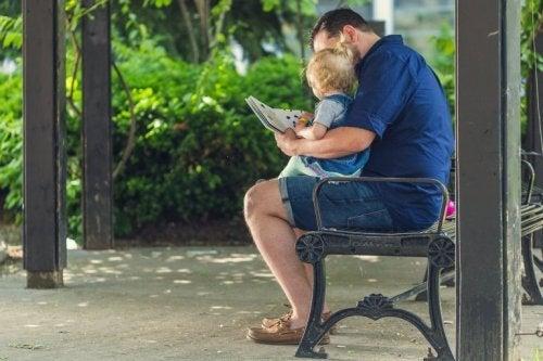 Pai ensinando uma criança a ler no parque.