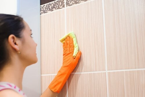 Mulher limpando parede manchada