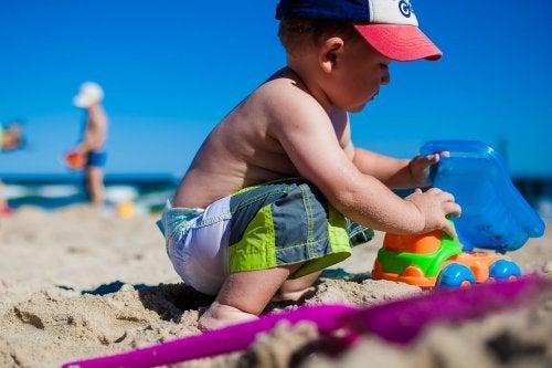 Menino brincando na areia da praia