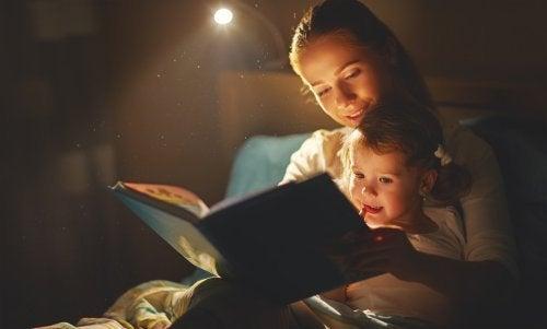 Mãe lendo uma história para sua filha para superar a morte de seu animal de estimação