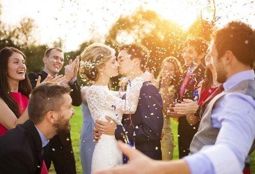 Casal de noivos beijando no casamento com padrinhos e parentes
