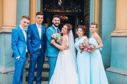 Casal de noivos e padrinhos posando na porta da igreja