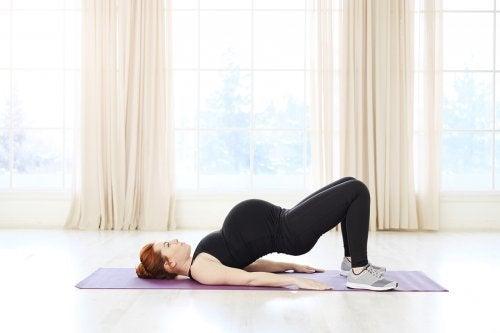 Mulher grávida se exercitando com pilates