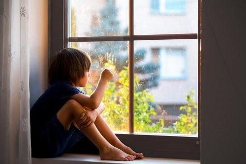 Criança triste olhando pela janela.