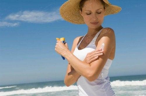 Mulher passando protetor solar no corpo