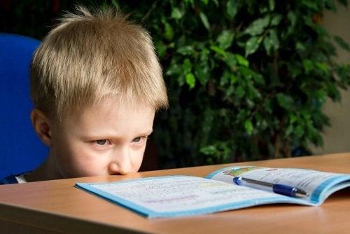 Criança distraída com dever de casa