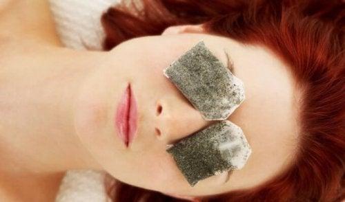 Mulher usando saquinhos de chá para desinflamar os olhos