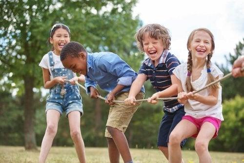 Crianças brincando de cabo de guerra fazendo atividade física