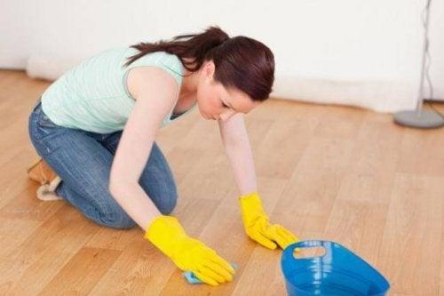 Mulher tentando limpar resíduos pegajosos do piso