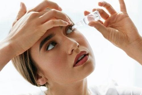 Mulher pingando colírio de oximetazolina oftálmica
