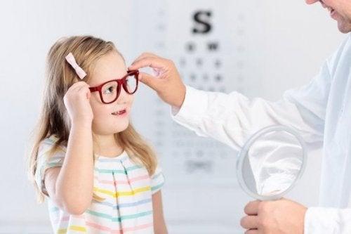 Menina experimentando óculos