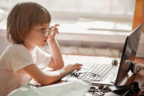 Menino com óculos no computador