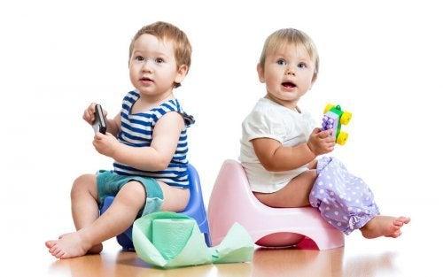 Bebês sentados no penico