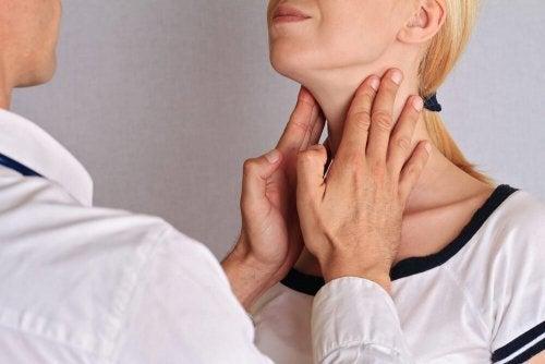 Pescoço da mulher sendo palpado por um médico para controle da tireoide.