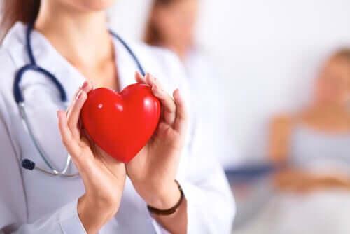 Médica segurando coração.