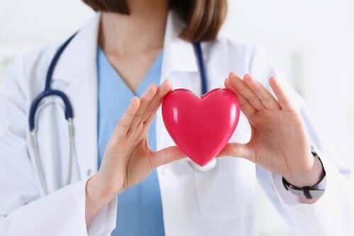 Médico com um coração nas mãos.