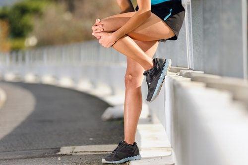 Atleta mulher segurando o joelho