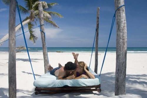 Casal em uma cama na praia beijando