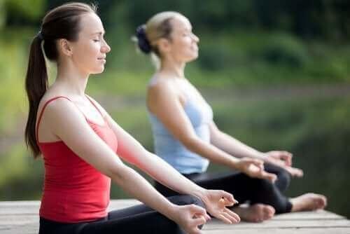 Duas mulheres fazem ioga ao ar livre no outono
