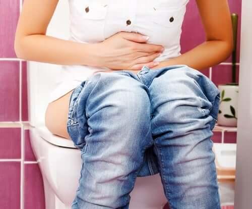 Mulher sentada no vaso sanitário com as mãos no abdômen