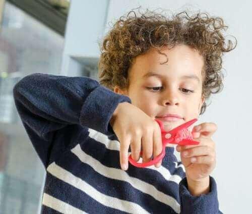 Criança usando uma tesoura para fazer artesanato.