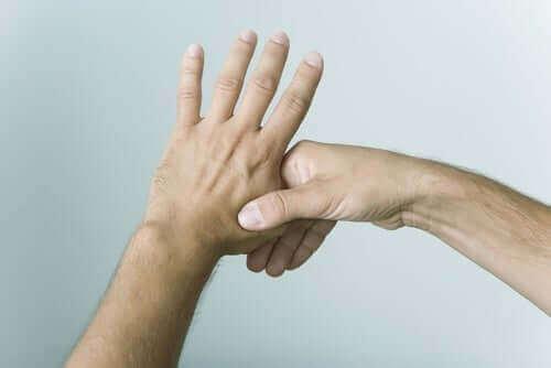 Mão segurando o polegar da outra mão