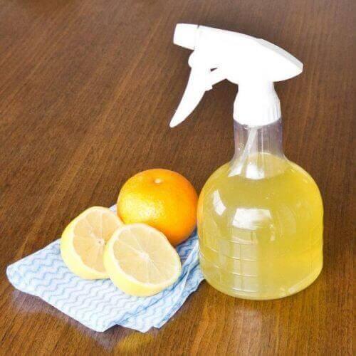 Produto de limpeza em um borrifador e laranjas
