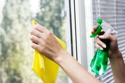 Mãos de limpar o vidro com um pulverizador e um pano