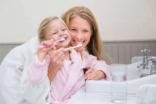 Mãe ensinando a filha a escovar os dentes