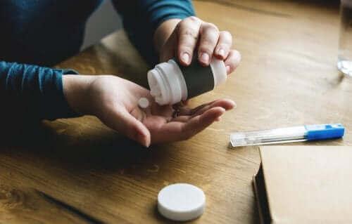 Uma pessoa que pega uma pílula de um recipiente anti-inflamatórios não esteroides