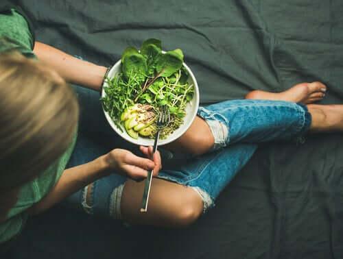 Adolescente comendo salada