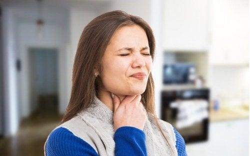 Mulher sentindo dor ao engolir