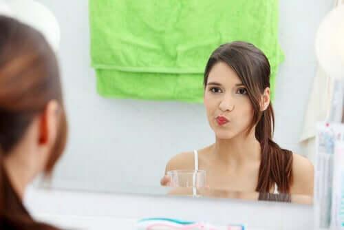 Mulher usando enxaguante bucal