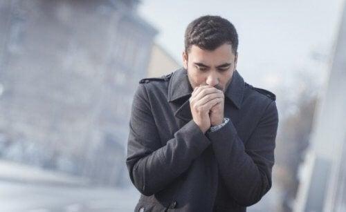 Homem aquecendo as mãos no inverno