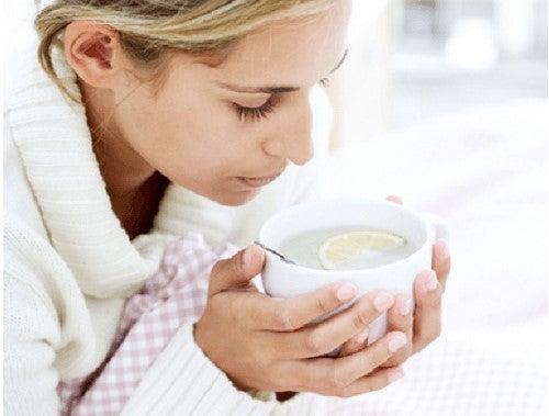 Mulher gripada tomando chá