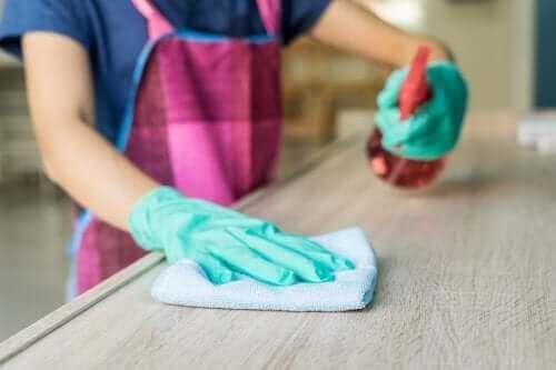 Limpa móveis de madeira com um spray e um pano