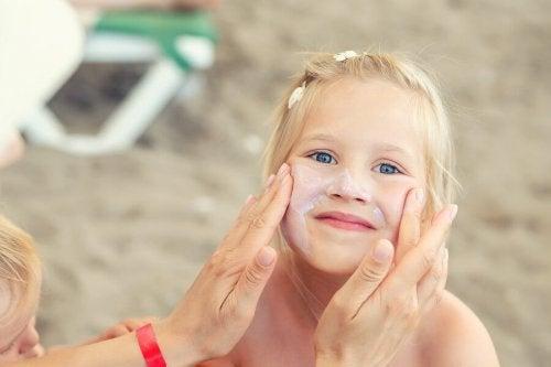 Criança passando protetor solar